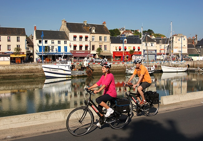 Couple cycling through Port-en-Bessin on the D-Day Landing Beaches cycle route