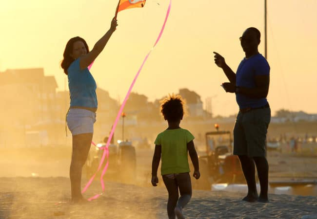A family on the beach at sunset with a kite