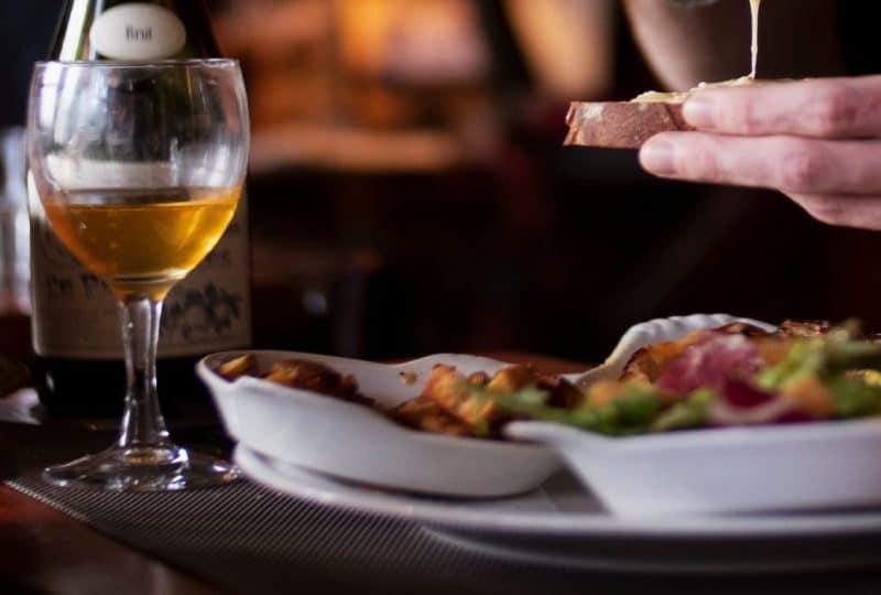 2 verres de cidre et un plat avec spécialité au fromage normand _ main d'une personne faisant une tartine de fromage normand